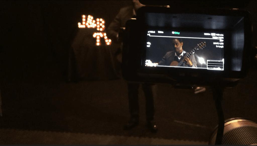 camera monitor showing man playing guitar